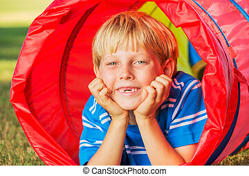 Cute Young Boy Playing Outside in Colorful Tunnel