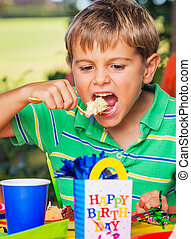 Boy Eating Cake - Happy Young Boy Eating Cake at Birthday...