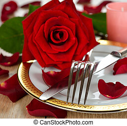 romantic Dinner - Cutlery and rose on a brown table