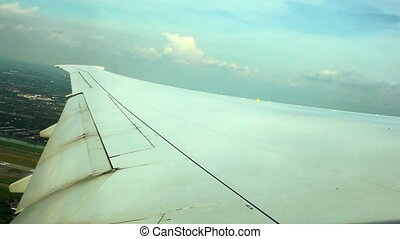 WINDOW VIEW OF WING PLANE OVER GROU