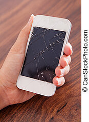 Hand Holding Smartphone With Cracked Screen - Close-up Of...