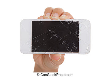 Hand holding smartphone with cracked screen over white...