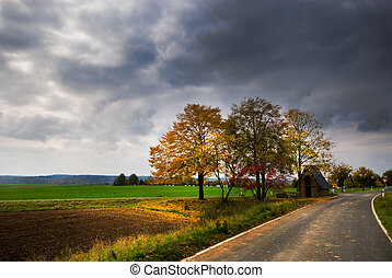 autumn landscape - a road through an autumn landscape in...