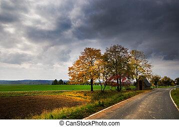autumn landscape - a road through an autumn landscape in...