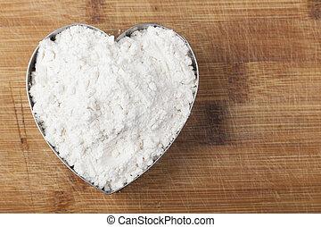 Flour Heart - Flour shape heart in a mold on brown wood...