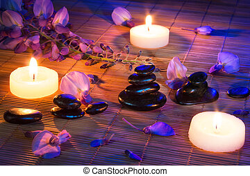 black stones, violet flowers, and candles on matbamboo