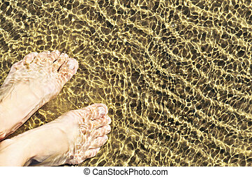 Feet in shallow water - Bare feet wading in clear shallow...