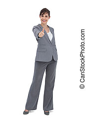 Young businesswoman looking at camera giving thumb up