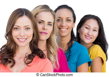 Smiling models in a line posing with colorful t shirts on...