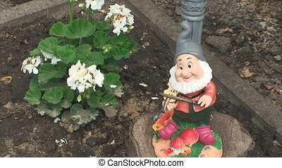 figure of a dwarf standing near the flower in the country...