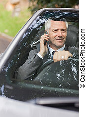 Smiling businessman on the phone driving expensive cabriolet...