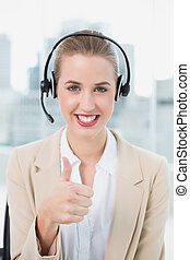 Smiling pretty call centre agent in bright office wearing...