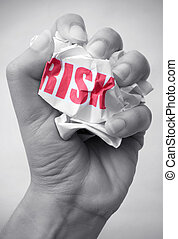 Minimizing risk - Hand squashing a crumpled piece of paper...