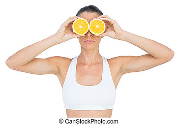 Fit woman holding slices of orange on her eyes on white...