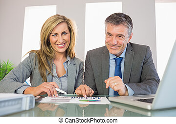 Two pleased business people smiling at camera analyzing a...