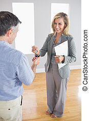 Laughing blonde realtor holding a briefcase and giving a key...