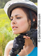 Athletic woman adjusting her bike helmet in the countryside