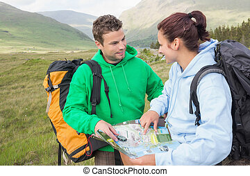 Happy couple resting after hiking uphill and consulting map...