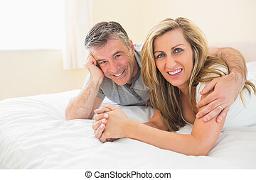 Happy couple lying on a bed looking at camera - Happy couple...