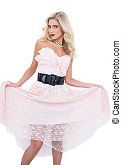 Lovely blonde model in pink dress holding her dress on white...