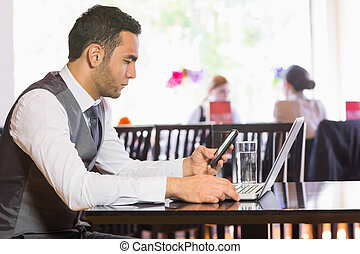 Serious businessman using phone while working on laptop in a...