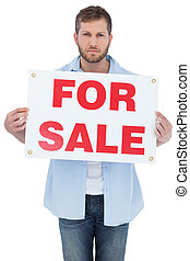 Serious young man holding a for sale sign