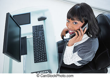 High angle view of smiling pretty businesswoman on the phone