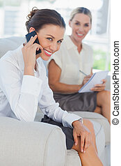 Businesswoman having a phone call while her colleague...