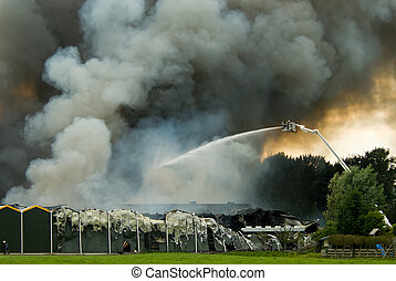 Firefighters in action - a huge fire with firefighters in...