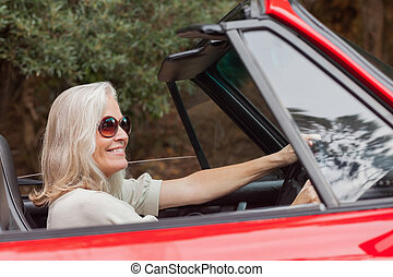 Happy mature woman with sunglasses driving red convertible...