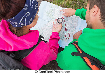 Couple using compass and map on their hike in the country