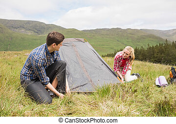 Happy couple pitching their tent in the countryside