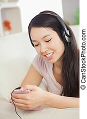 Relaxing asian girl lying on the sofa and listening to music...