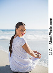 Rear view of smiling woman on the beach on a sunny day looking over shoulder at camera