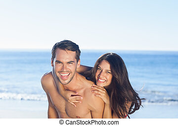 Happy couple playing together on the beach