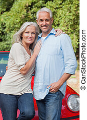 Smiling mature couple posing against their red cabriolet