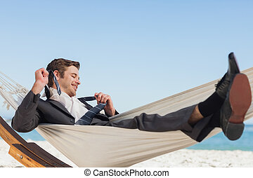 Smiling businessman lying in hamock taking off his tie at...