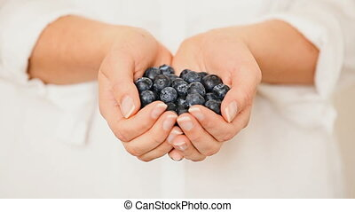 Handful of blueberries getting poured down from female hands...