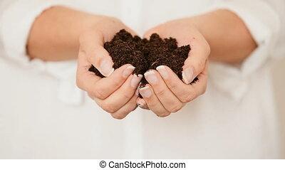 Hands holding black Soil - Caucasian female model pouring...