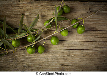 olive branch on the wooden table - Green olive branch on the...
