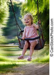 girl having fun on a swing - cute one year old girl having...