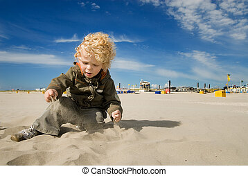 cute boy playing with sand on the beach