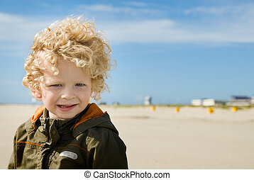 cute boy on the beach looking at the camera