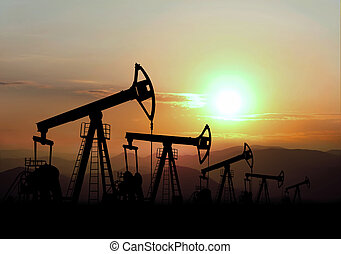 oil field and pump jack on sunset