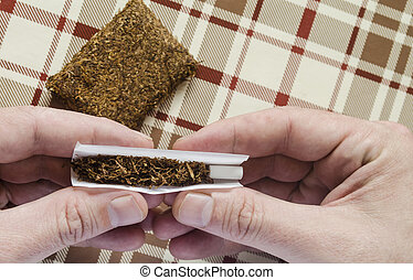 rolling a tobacco cigarette on check background