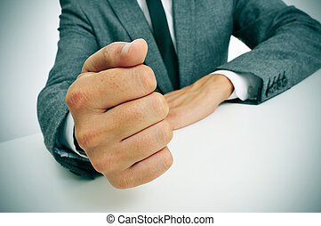 man in suit banging his fist on the desk