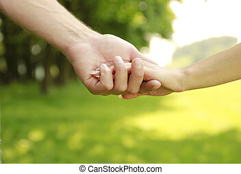 two hands of a loving couple on nature - a two hands of a...