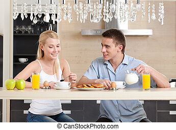 Couple has a snack in the kitchen