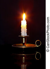 Candle in brass chamberstick - A single burning candle in a...