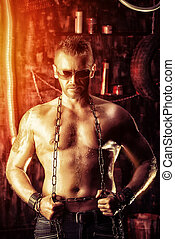 muscular worker - Handsome muscular man with chain in the...
